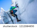 Small photo of Epic shot of an ice climber climbing on a wall of ice. Mountaineer, climber or alpinist on an adventure extreme ascent with ice axe and crampons. Alpine extreme climbing on a serac or crevasse.