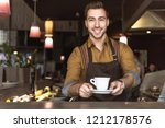 smiling young barista holding... | Shutterstock . vector #1212178576