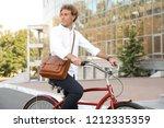 attractive man riding bike on...   Shutterstock . vector #1212335359