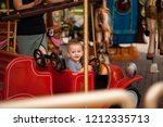 cheerful child on the carousel. ... | Shutterstock . vector #1212335713