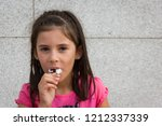 Small photo of Smiling little girl eating chocolate ice cream. Young kid portrait on pink t shirt with full mouth eating cold dessert. Dirty, mess, fun, childhood joy concepts