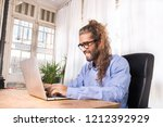 man with lonh hair working with ... | Shutterstock . vector #1212392929