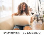 man with lonh hair working with ... | Shutterstock . vector #1212393070