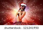 Young brunette woman in christmas wear with earphones - stock photo