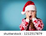 shocked christmas girl in santa ... | Shutterstock . vector #1212517879