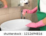 woman cleaning tap with rag in... | Shutterstock . vector #1212694816