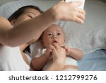 mom take a photo with baby boy. | Shutterstock . vector #1212799276