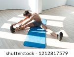 muscular man stretches at the...   Shutterstock . vector #1212817579