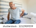 Small photo of Senior man suffering from back pain at home while wife sleeping on bed. Old man with backache having difficulty in getting up from bed. Suffering from backache and sitting on bed in the morning.