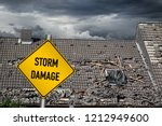 yellow damage warning sign in front of roof of house damaged by heavy hurricane tornado storm