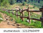 wooden palisade along nature... | Shutterstock . vector #1212960499