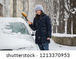 woman removing snow from car... | Shutterstock . vector #1213370953