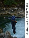 man jumping in wild river... | Shutterstock . vector #1213771576