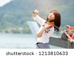 Beautiful woman hold violin on nature view background, in emotion feeling committed.