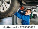 mechanic repairs the suspension ... | Shutterstock . vector #1213880899