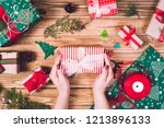girl decorates a christmas gift ...   Shutterstock . vector #1213896133