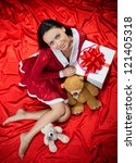 Portrait of a smiling brunette woman with toys and Christmas present on red background, view from above - stock photo