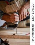 carpenter drills a hole with an ... | Shutterstock . vector #1214164120