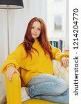 Small photo of serious pert attractive young woman sitting in a yellow armchair in her socks staring at the camera with an intent expression