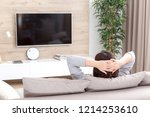 young woman watching tv in the... | Shutterstock . vector #1214253610