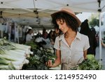 beautiful woman buying kale at... | Shutterstock . vector #1214952490