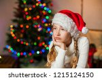 sad girl near christmas tree... | Shutterstock . vector #1215124150