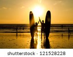 surfer couple in silhouette... | Shutterstock . vector #121528228