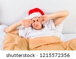 tired young man in santa hat in ... | Shutterstock . vector #1215572356