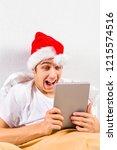 happy young man in santa hat... | Shutterstock . vector #1215574516