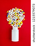 pills and vial on the red... | Shutterstock . vector #1215579073