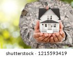 soldier holding a model of house | Shutterstock . vector #1215593419