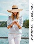 cute girl on lake using... | Shutterstock . vector #1215627550