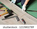 man installs new laminate... | Shutterstock . vector #1215802789