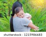 asian mother carrying her... | Shutterstock . vector #1215986683
