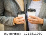 two women keeping two cups of... | Shutterstock . vector #1216511080