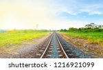 Small photo of railway tracks in a rural area with bright moring sunrise, panorama view