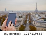 holding cellphone with paris in ... | Shutterstock . vector #1217119663