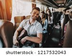 Small photo of Young Handsome Man Relaxing in Seat of Tour Bus. Attractive Smiling Man Sitting on Passenger Seat of Tourist Bus and Holding Backpack. Traveling and Tourism Concept. Happy Travelers on Trip