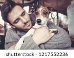 man cuddling with his terrier... | Shutterstock . vector #1217552236