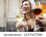 a woman drinks white wine at a... | Shutterstock . vector #1217627500