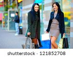 happy girls with shopping bags in city street - stock photo