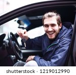 man showing keys to a new car. | Shutterstock . vector #1219012990