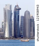 Stock photo a dhow passes beneath some of the most massive buildings in doha qatar shortly before sunset in 121908943