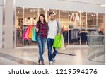 happy couple carrying bags in... | Shutterstock . vector #1219594276