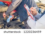 Auto mechanic perform vehicle checkup while service advisor take notes - Professional Auto Service Technician - concept of inspecting and taking care of the car - stock photo