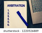 Small photo of Text sign showing Arbitration. Conceptual photo Use of an arbitrator to settle a dispute Mediation Negotiation Open notebook squared page black marker computer keyboard wooden background.