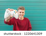 smiling young gamer with a... | Shutterstock . vector #1220641309