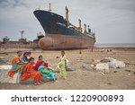 Small photo of Alang, India, September 2008. A group of women sit next to a large tonnage cargo ship stranded on the beach waiting to be scrapped.