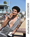 happy young man eating a slice... | Shutterstock . vector #1221012850
