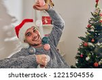 man sitting on a couch and... | Shutterstock . vector #1221504556